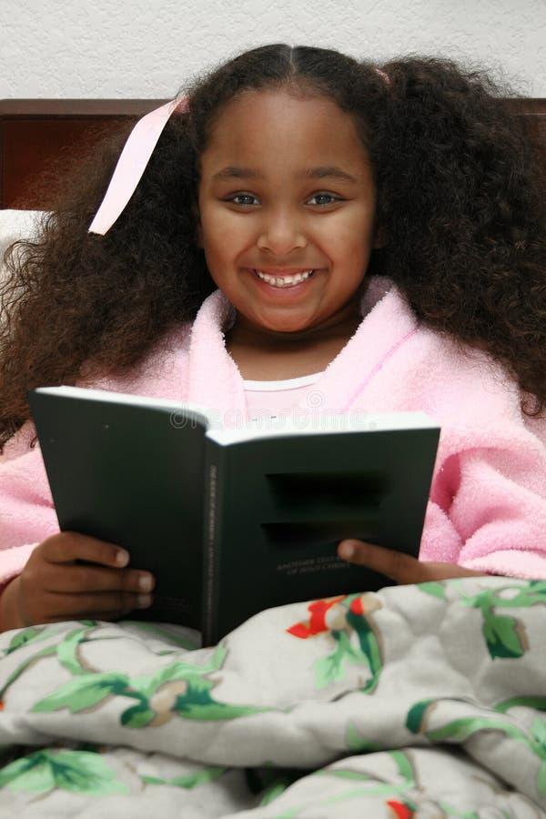 Girl reading in bed. Smiling multi-racial girl sat in bed reading stock image