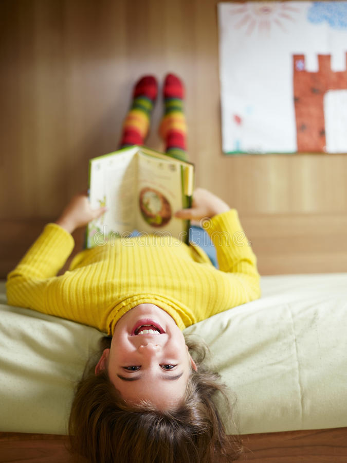 Girl reading book. Girl lying on bed and reading book