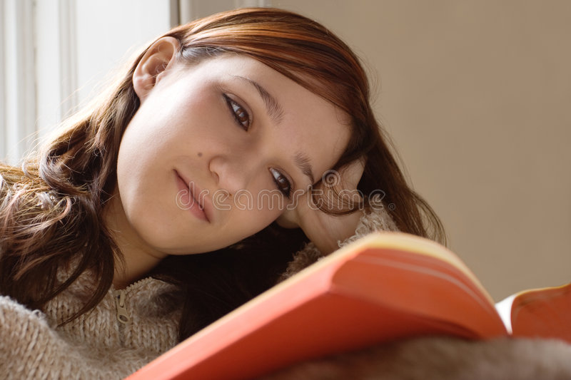 Girl reading book. Beautiful girl relaxing whilst reading a book stock images