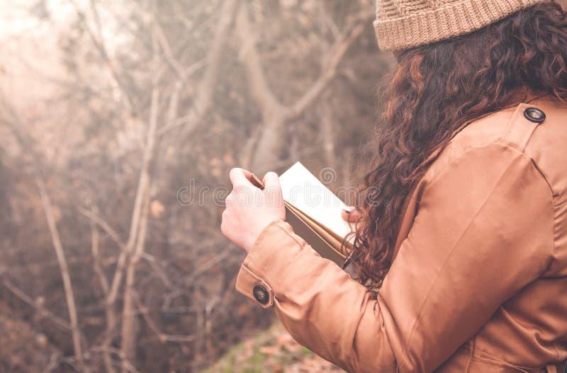 Girl reading book in the autumn park. stock photos