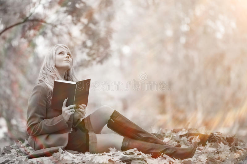 Girl reading book in autumn park royalty free stock photo