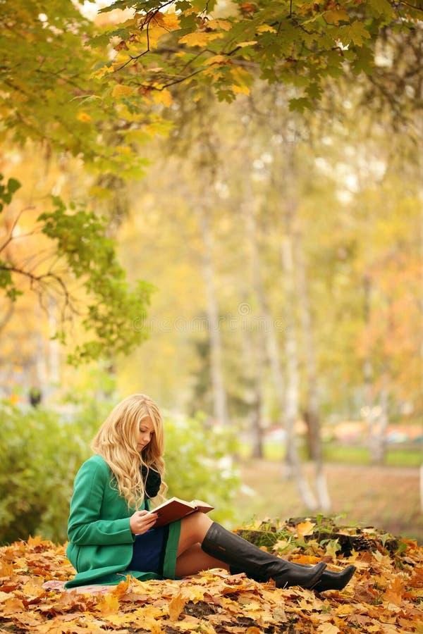 Girl reading book in autumn park stock photo