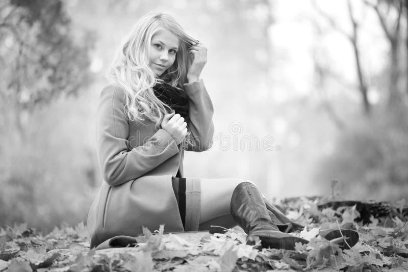 Girl reading book in autumn park stock photos