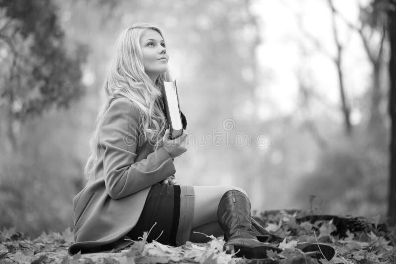 Girl reading book in autumn park royalty free stock photos