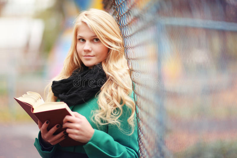 Girl reading book in autumn park stock images