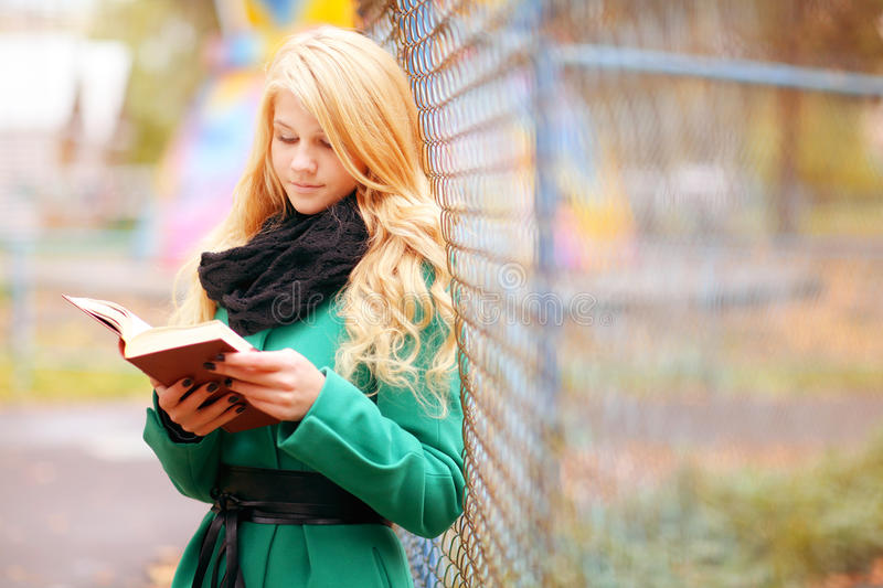 Girl reading book in autumn park stock image