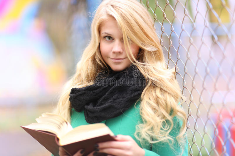 Girl reading book in autumn park royalty free stock images