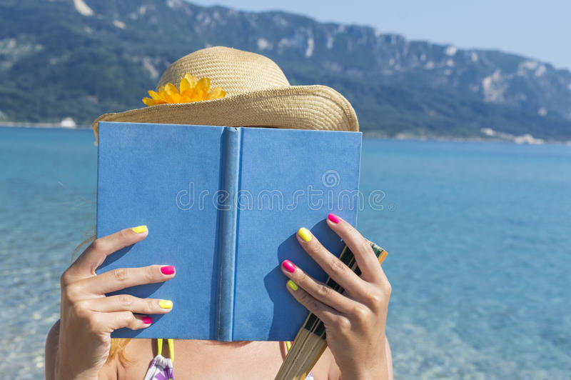 Girl reading a book on the beach stock photo