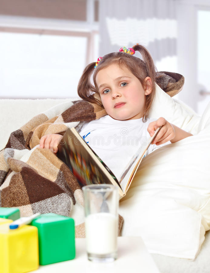 Girl reading a book in bed stock photography