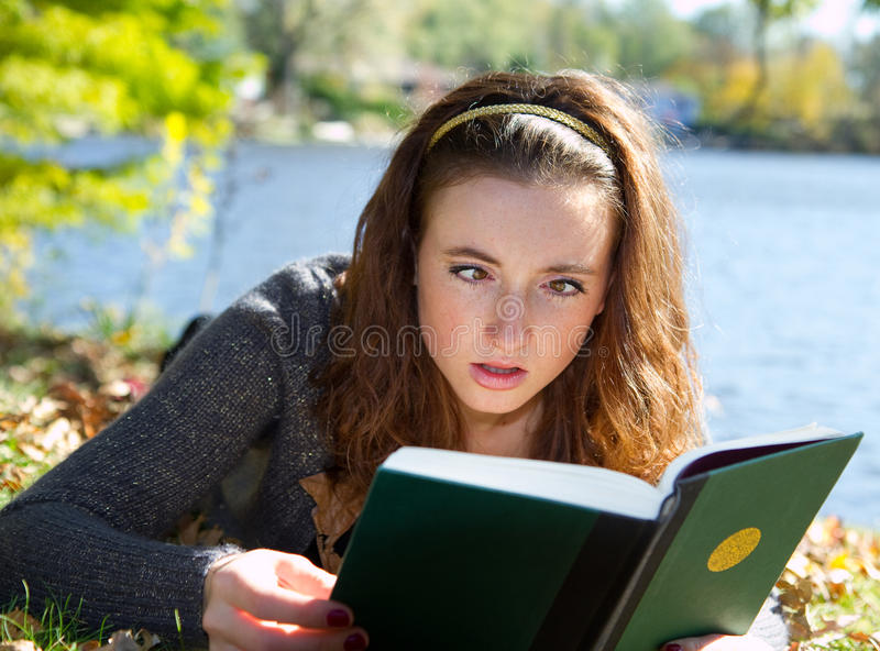 Girl reading book cross eyed in confusion royalty free stock photography