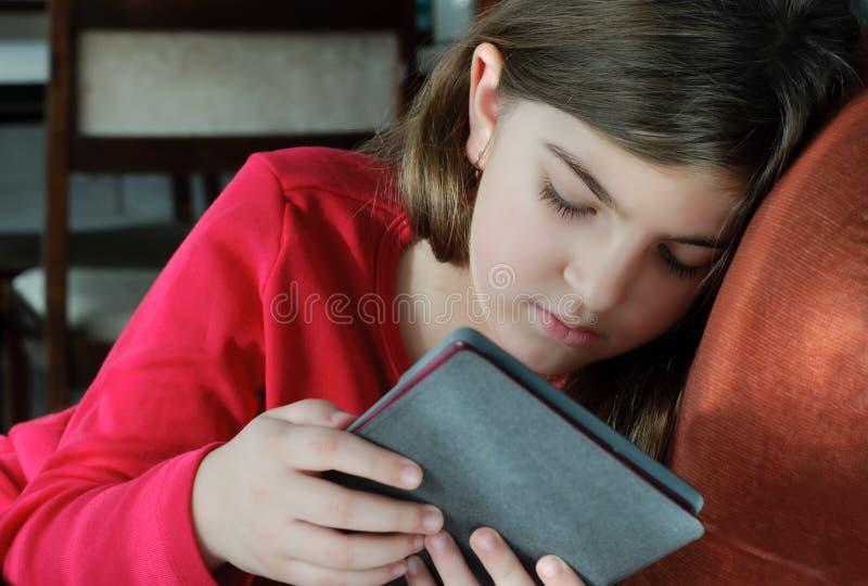 Girl Reading Book on E-Reader stock photography