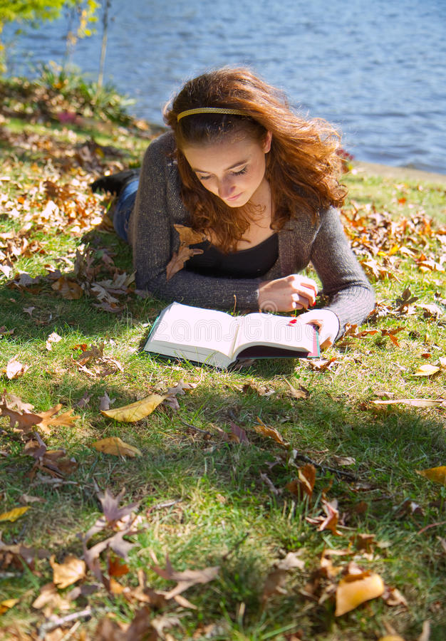 Girl reading book among fall leaves stock image