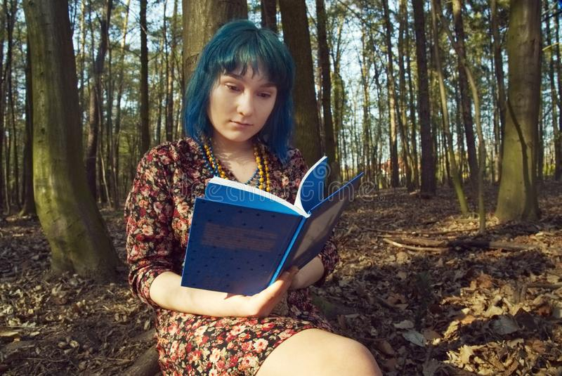 The girl is reading a book in the forest. The girl in blue hair is reading a book in the forest stock photography