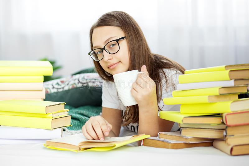 A girl is reading a book with glasses. Teenager drinks coffee. Concept of education, hobby and study and world book day royalty free stock photography