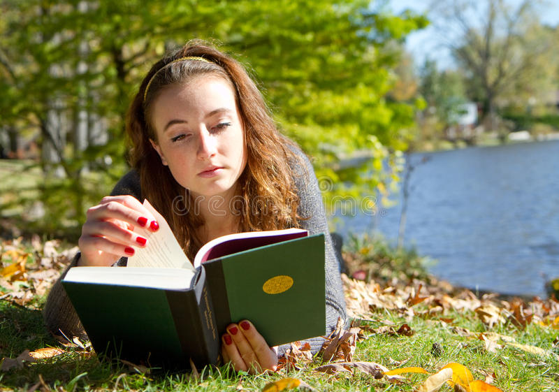 Girl reading book while laying down stock photos