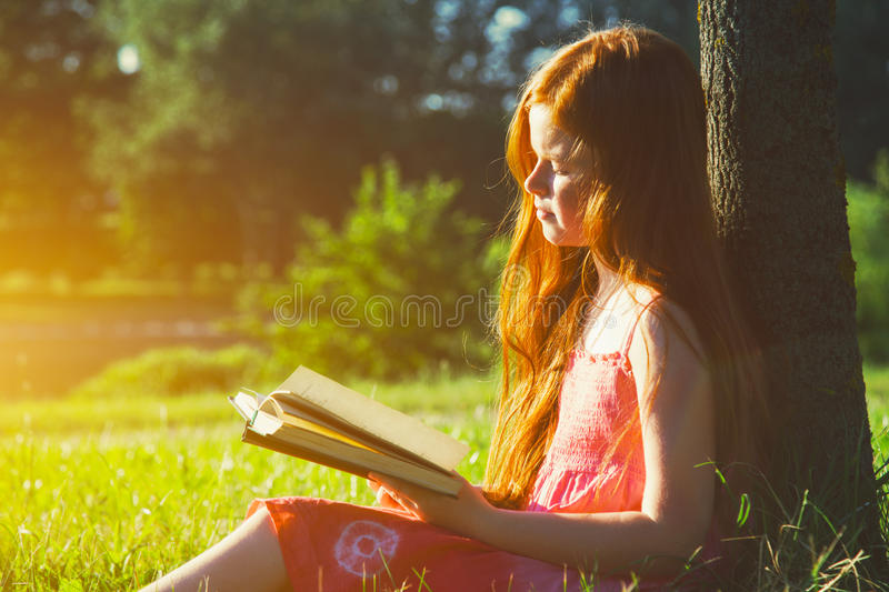 Girl reading book. Little redhead girl reading book at nature stock photos