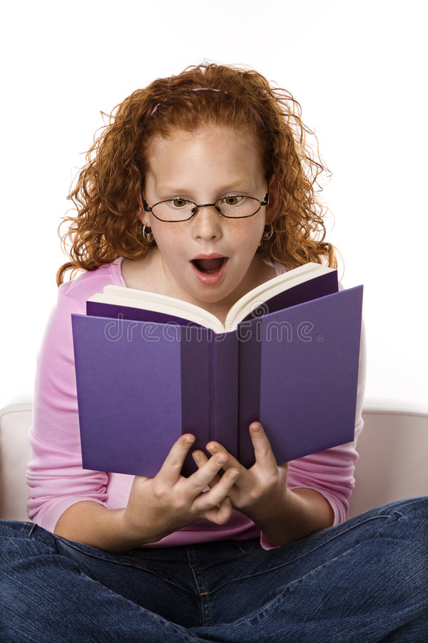 Girl reading book looking surprised. stock photography