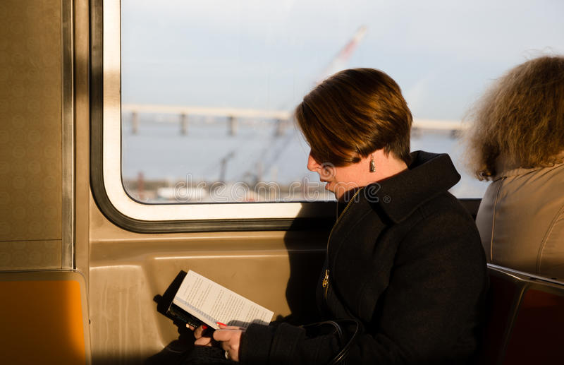 Girl reading a book in the New York subway wagon royalty free stock photos