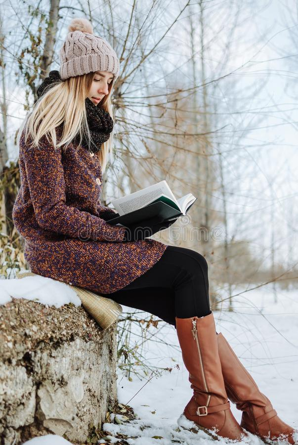 Girl reading book outdoors in winter royalty free stock photos