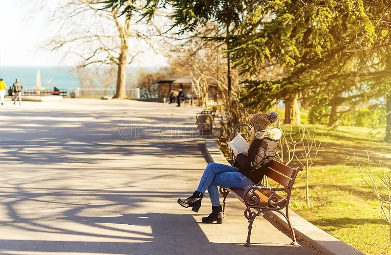 Girl reading a book in the park. A girl sits on a bench and reads a book in a seaside park on a warm and sunny spring day stock images