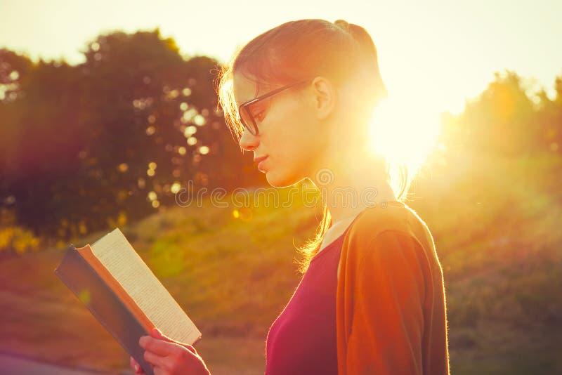 Girl reading book. In summer sunset light royalty free stock image