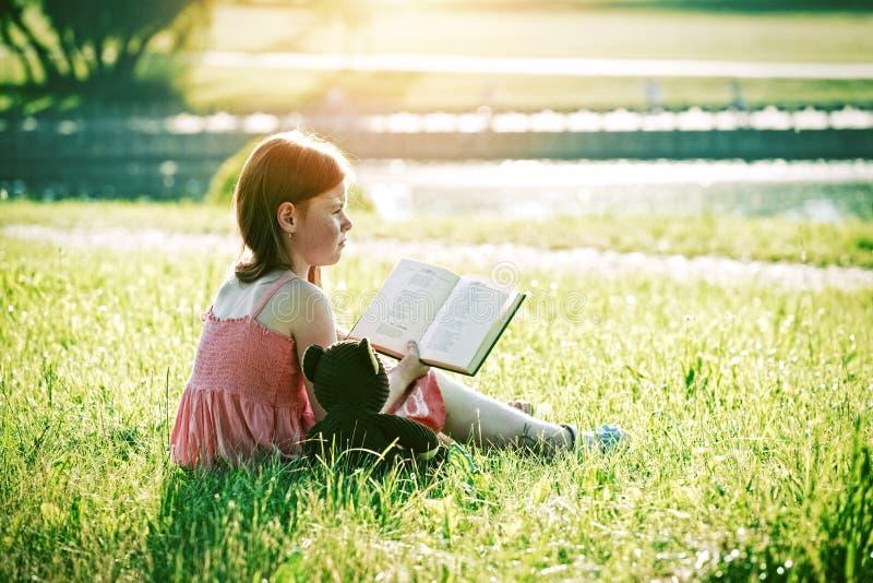 Girl reading book with teddy bear toy stock photos