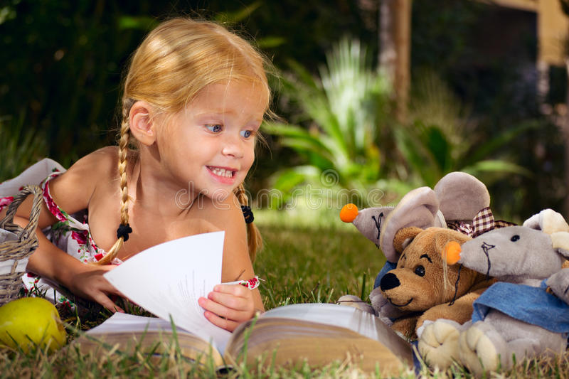 Girl reading a book with the toys in the garden royalty free stock image