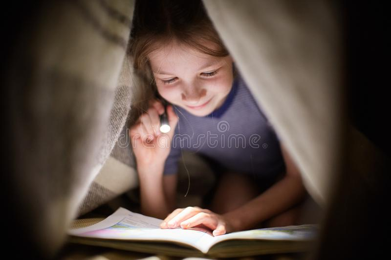 Little girl is reading a book under a blanket with a flashlight in a dark room at night stock images