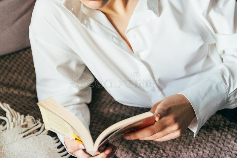 Girl reading a book in a warm blanket. woman lies, lay down on the bed, a blanket, a sofa, a couch and holds a book. Girl reading. A book. education, recreation stock image