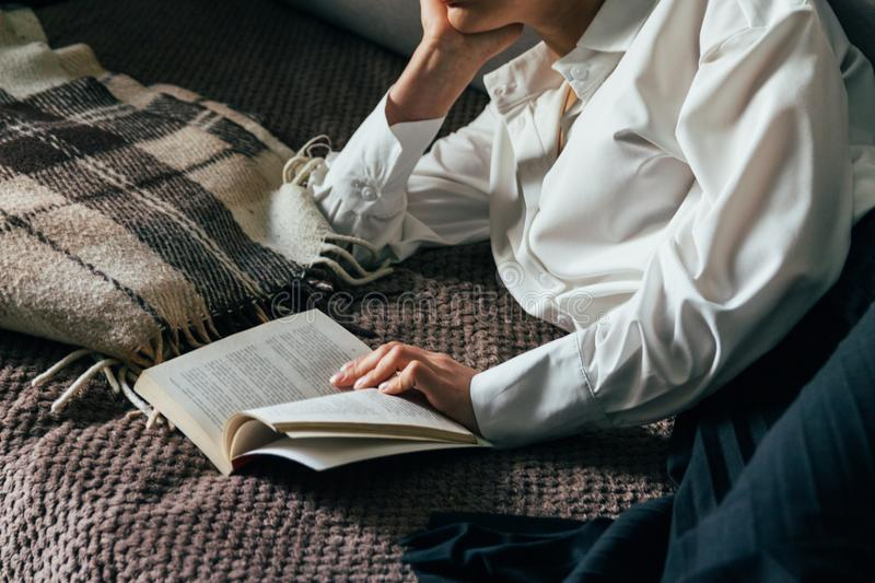 Girl reading a book in a warm blanket. woman lies, lay down on the bed, a blanket, a sofa, a couch and holds a book. Girl reading. A book. education, recreation royalty free stock image