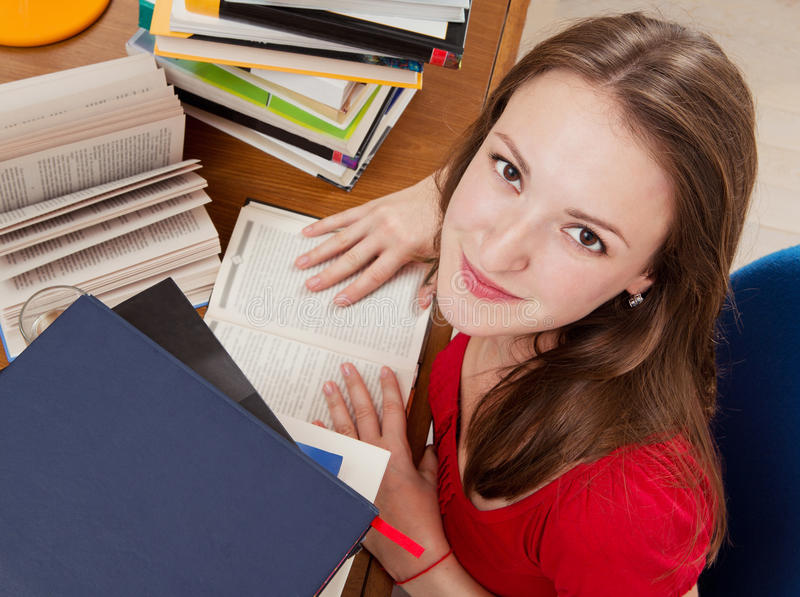 Girl is reading books. Young woman with lots of books. Reading a books stock photo