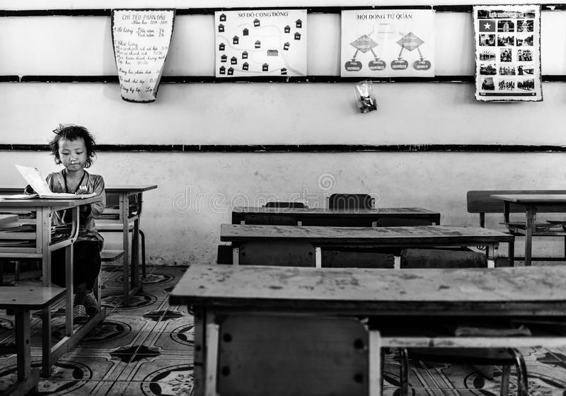 Girl reading books inside classroom in a small village, Sapa, Vietnam stock images