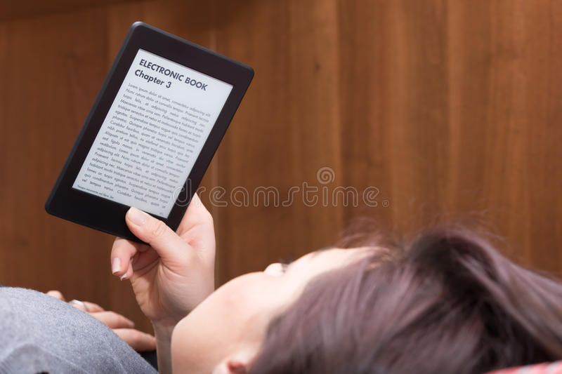 Girl is reading with an Ebook Reader on the bed. Brunette GIrl is focused reading an electronic bestseller with her Ebook Reader while she is on the bed. The stock photo
