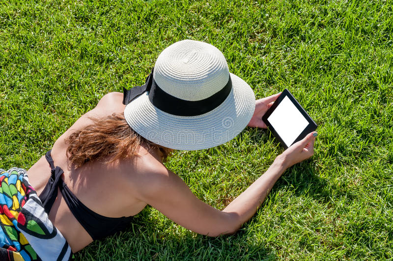 Girl reading electronic book on grass stock photo