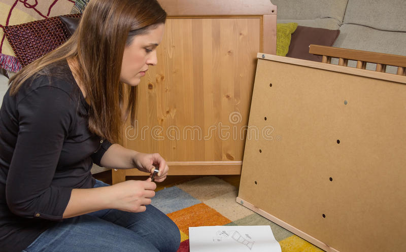 Girl reading instructions to assemble furniture. Concentrated girl with tools reading the instructions to assemble a new furniture for home stock images