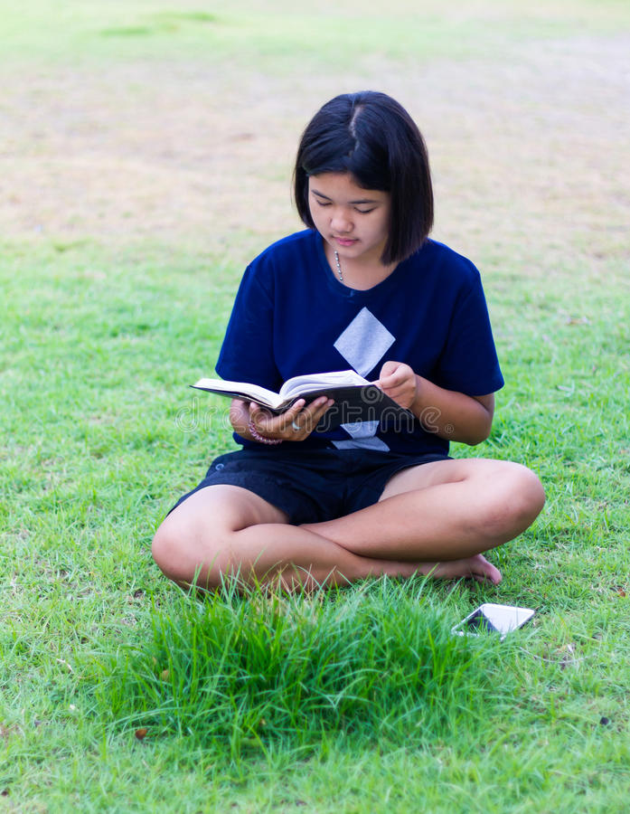 Girl reading on the lawn. royalty free stock image