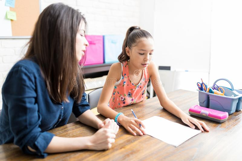 Girl Reading Lesson On Paper By Private Tutor At Table royalty free stock image