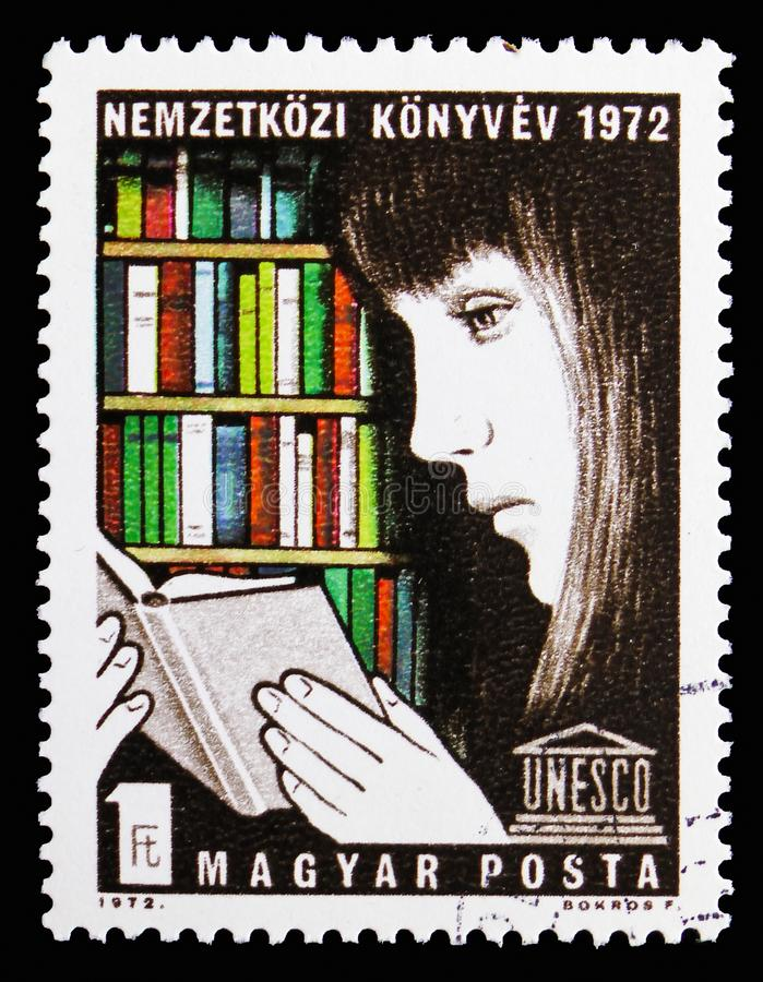 Girl reading in a library, International Book Year serie, circa 1972 stock images