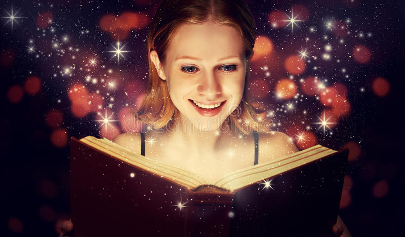 Girl reading magic book. Girl reading a magic book royalty free stock image
