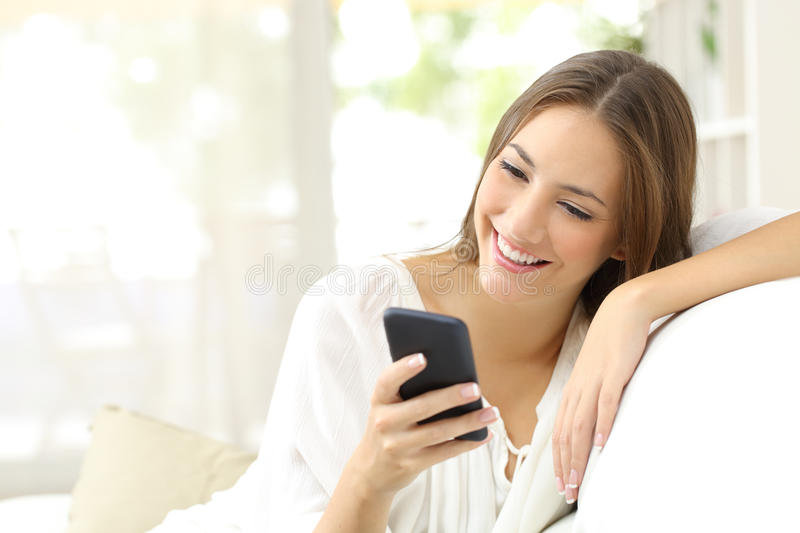 Girl reading message in a smart phone. Happy girl reading a message in a smart phone sitting on a couch at home