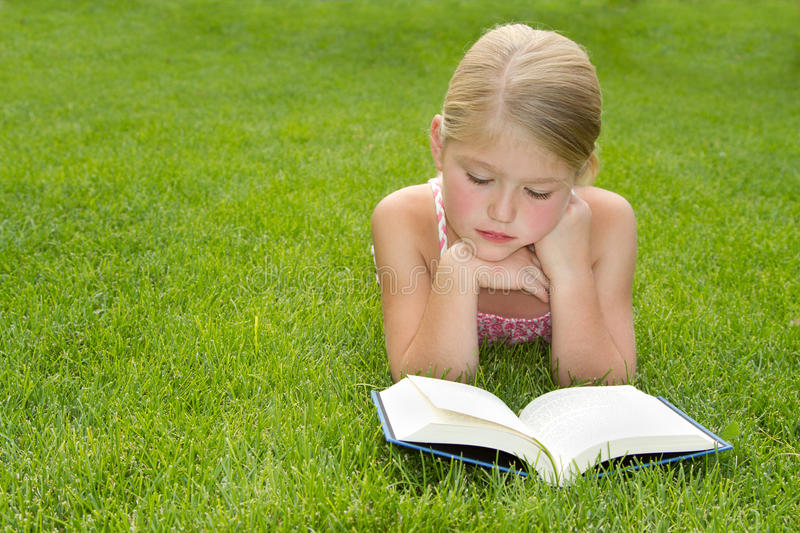 Girl Reading Outdoors Stock Photo