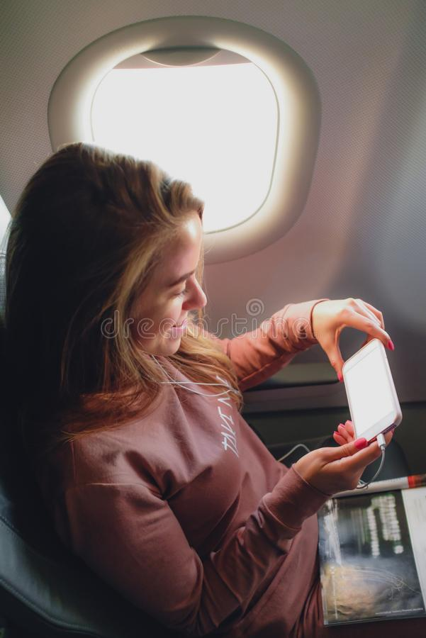 Girl is reading from smartphone in airplane stock photos
