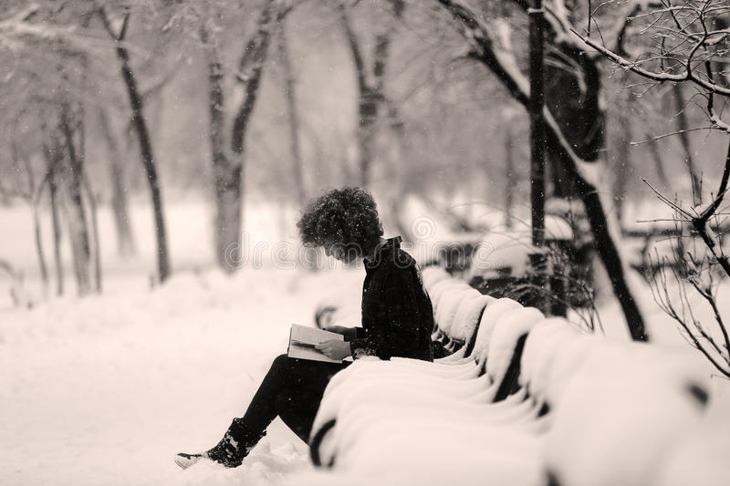 Girl reading in the snow, sitting on a bench. Girl reading a book in the snow, park in December stock photos