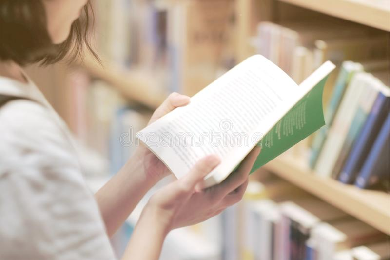 A girl reading some book in the bookstore. University, knowledge, education, student, library, young, study, female, college, studying, beautiful, pretty stock photos