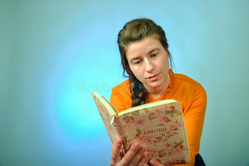 A girl reads the Bible while sitting on a chair on a blue background. The inscription in Russian -. `Bible` on the book stock photography