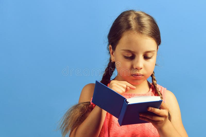 Girl reads blue book. School girl with concentrated face stock images