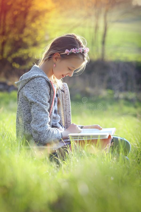 The girl reads a book in the nature stock images