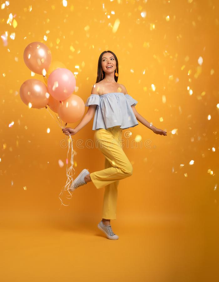 Girl ready for a party with balloon. Joyful an happiness expression. Yellow background royalty free stock photos