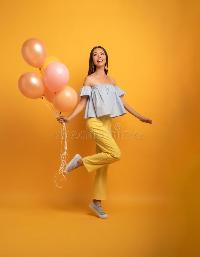 Girl ready for a party with balloon. Joyful an happiness expression. Yellow background. Brunette girl ready for a party with balloon. Joyful an happiness royalty free stock image
