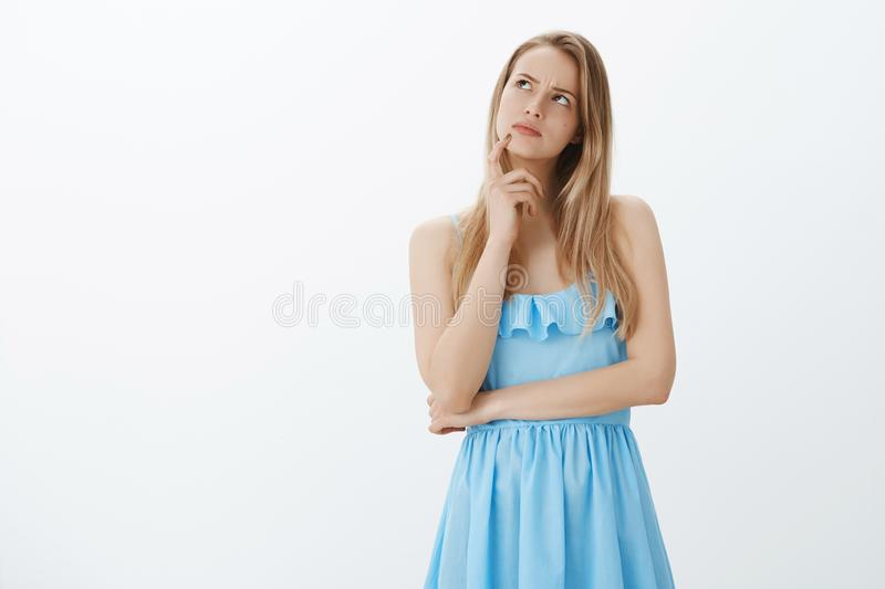 Girl recalling conversation starting overthink, getting triggered. Thoughtful hesitant and focused young attractive. Woman with blond hair in blue dress looking stock images